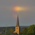 """Kirchturm mit Regenbogenfarben -- Nach dem Regen am 9.8.2019 gab es kurz vor Sonnenuntergang ein geradezu magisches Licht, Regenbogensegmente verpassten dem Kirchturm von St. Hubertus Roetgen einen bunten """"Disco-Hintergrund""""."""